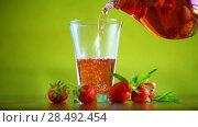 Купить «Sweet compote of ripe red strawberries in a glass decanter on a table», видеоролик № 28492454, снято 31 мая 2018 г. (c) Peredniankina / Фотобанк Лори