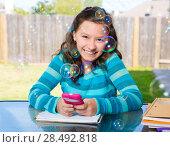 Купить «American latin teen girl with smartphone doing homework on backyard», фото № 28492818, снято 16 июля 2019 г. (c) Ingram Publishing / Фотобанк Лори