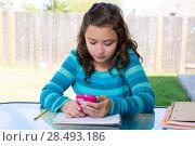 Купить «American latin teen girl with smartphone doing homework on backyard», фото № 28493186, снято 16 июля 2019 г. (c) Ingram Publishing / Фотобанк Лори
