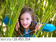 Beautiful little girl playing in nature  peeping from green canes. Стоковое фото, агентство Ingram Publishing / Фотобанк Лори