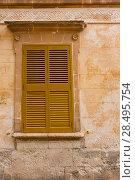 Ciutadella Menorca wooden shutter window on grunge yellow downtown wall at Balearic islands (2013 год). Стоковое фото, фотограф Tono Balaguer / Ingram Publishing / Фотобанк Лори