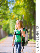 Купить «Blond explorer kid girl walking with backpack hiking in autumn trees track holding stick», фото № 28497134, снято 5 октября 2013 г. (c) Ingram Publishing / Фотобанк Лори
