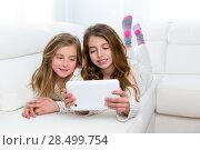 Купить «Children sister friends kid girls playing together with tablet pc lying on white sofa», фото № 28499754, снято 9 февраля 2014 г. (c) Ingram Publishing / Фотобанк Лори