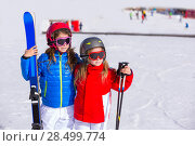 Купить «Kid girls sister in winter snow with ski equipment helmet goggles poles», фото № 28499774, снято 26 января 2014 г. (c) Ingram Publishing / Фотобанк Лори