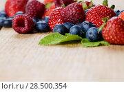 Купить «Strawberries raspberries and blueberries on the wooden table macro», фото № 28500354, снято 16 августа 2013 г. (c) Ingram Publishing / Фотобанк Лори