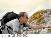 Купить «Man with backpack climbing over stones», фото № 28500602, снято 4 апреля 2020 г. (c) Ingram Publishing / Фотобанк Лори