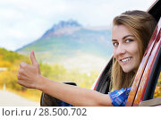 Купить «Happy driver woman shows thumb up against mountains background. Car insurance concept», фото № 28500702, снято 26 сентября 2013 г. (c) Ingram Publishing / Фотобанк Лори