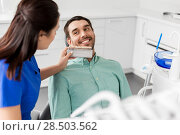 Купить «dentist choosing tooth color for patient at clinic», фото № 28503562, снято 22 апреля 2018 г. (c) Syda Productions / Фотобанк Лори