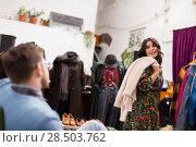 Купить «woman posing for boyfriend at clothing store», фото № 28503762, снято 30 ноября 2017 г. (c) Syda Productions / Фотобанк Лори