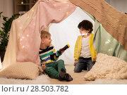 Купить «happy boys with torch light in kids tent at home», фото № 28503782, снято 18 февраля 2018 г. (c) Syda Productions / Фотобанк Лори