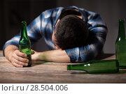 Купить «drunk man with beer bottles on table at night», фото № 28504006, снято 24 ноября 2017 г. (c) Syda Productions / Фотобанк Лори