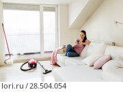 Купить «woman with smartphone and vacuum cleaner at home», фото № 28504054, снято 29 апреля 2018 г. (c) Syda Productions / Фотобанк Лори