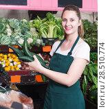 Купить «Seller female is holding green cucumbers», фото № 28510774, снято 29 апреля 2018 г. (c) Яков Филимонов / Фотобанк Лори