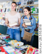 Купить «smiling woman with happy girl taking literature books in store with prints», фото № 28510818, снято 9 мая 2017 г. (c) Яков Филимонов / Фотобанк Лори