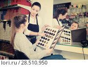 Купить «Young female hairdresser with woman client looking samples of hair dye in beauty salon», фото № 28510950, снято 31 марта 2018 г. (c) Яков Филимонов / Фотобанк Лори