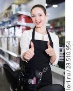 Купить «Professional positive female hairdresser holding thumbs up in salon», фото № 28510954, снято 31 марта 2018 г. (c) Яков Филимонов / Фотобанк Лори