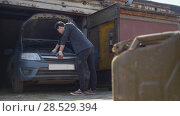 Купить «Canister stands in front of young man repairs car in garage», фото № 28529394, снято 18 июня 2019 г. (c) Константин Шишкин / Фотобанк Лори
