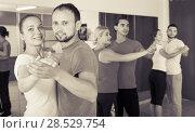 Купить «Pair dancing tango in dancing studio», фото № 28529754, снято 20 июля 2018 г. (c) Яков Филимонов / Фотобанк Лори