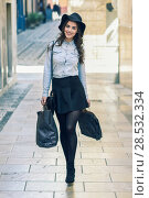 Купить «Beautiful brunette young woman wearing short skirt and denim shirt walking on the street with shopping bags», фото № 28532334, снято 10 марта 2015 г. (c) Ingram Publishing / Фотобанк Лори