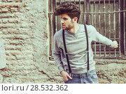 Купить «Portrait of young man wearing suspenders in urban background», фото № 28532362, снято 8 апреля 2014 г. (c) Ingram Publishing / Фотобанк Лори