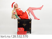 Купить «Beautiful happy blonde woman in Santa Claus clothes and striped socks moving her legs. Young funny girl with blue eyes carrying a sack of santa claus, isolated on white», фото № 28532570, снято 23 августа 2017 г. (c) Ingram Publishing / Фотобанк Лори