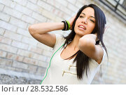 Portrait of young attractive girl in urban background hearing music with headphones. Стоковое фото, фотограф Javier Sánchez Mingorance / Ingram Publishing / Фотобанк Лори