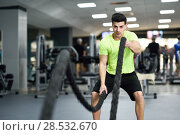Купить «Man with battle ropes exercise in the fitness gym. Young male wearing sportswear.», фото № 28532670, снято 4 декабря 2016 г. (c) Ingram Publishing / Фотобанк Лори