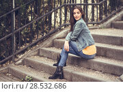 Купить «Young woman with nice hair wearing casual clothes in urban background. Happy girl with wavy hairstyle sitting in urban stairs.», фото № 28532686, снято 30 апреля 2017 г. (c) Ingram Publishing / Фотобанк Лори