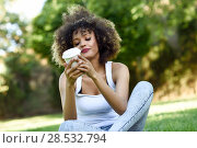 Купить «Beautiful young African American woman with afro hairstyle in urban park. Girl reading a take away glass of coffee sitting on grass wearing casual clothes.», фото № 28532794, снято 14 июня 2016 г. (c) Ingram Publishing / Фотобанк Лори