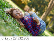 Beautiful woman with long blond curly hair. Enjoyment. Expressive Woman in checkered shirt and blue jeans with toothy Smile. Стоковое фото, фотограф Javier Sánchez Mingorance / Ingram Publishing / Фотобанк Лори