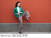 Купить «Young brunette woman, model of fashion, wearing green modern jacket and flower pants on red wall. Pretty caucasian girl with long wavy hairstyle. Female with red lips in urban background.», фото № 28532910, снято 11 марта 2017 г. (c) Ingram Publishing / Фотобанк Лори
