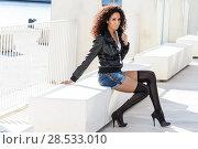 Купить «Black female, afro hairstyle, in urban background. Woman wearing denim shorts and leather jacket.», фото № 28533010, снято 11 декабря 2011 г. (c) Ingram Publishing / Фотобанк Лори