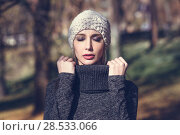 Купить «Young blonde woman standing in a park with autumn colors. Beautiful girl wearing winter gray dress and wool cap. Female with straight hair and eyes closed with dark eyeshadow.», фото № 28533066, снято 11 декабря 2016 г. (c) Ingram Publishing / Фотобанк Лори
