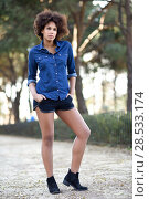 Купить «Young black woman with afro hairstyle standing in urban background. Mixed woman wearing blue shirt and shorts.», фото № 28533174, снято 10 декабря 2016 г. (c) Ingram Publishing / Фотобанк Лори