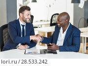 Black businessman shaking hands with a caucasian one wearing suit in a office. Two smiling men wearing blue suits working in an office with white furniture. Стоковое фото, фотограф Javier Sánchez Mingorance / Ingram Publishing / Фотобанк Лори