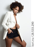 Купить «Young black woman with afro hairstyle possing near a white wall in her room. Mixed girl wearing blazer jacket and shorts.», фото № 28533290, снято 10 декабря 2016 г. (c) Ingram Publishing / Фотобанк Лори