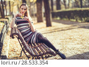 Купить «Young blonde woman sitting on a bench in the street of a park with autumn colors. Beautiful girl in urban background wearing striped dress and black tights. Female with straight hair holding an autumn leaf.», фото № 28533354, снято 11 декабря 2016 г. (c) Ingram Publishing / Фотобанк Лори