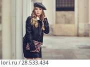 Купить «Blonde russian woman in urban background. Beautiful young girl wearing beret, black leather jacket and mini skirt standing in the street. Pretty female with long wavy hair hairstyle and blue eyes.», фото № 28533434, снято 24 января 2017 г. (c) Ingram Publishing / Фотобанк Лори