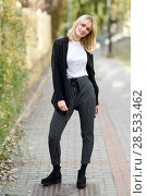 Купить «Pretty blonde woman smiling in urban background. Young girl wearing black blazer jacket and striped trousers standing in the street. Pretty female with straight hair hairstyle and blue eyes.», фото № 28533462, снято 22 января 2017 г. (c) Ingram Publishing / Фотобанк Лори