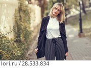 Купить «Beautiful blonde woman in urban background. Young girl wearing black blazer jacket and striped trousers standing in the street. Pretty female with straight hair hairstyle and blue eyes.», фото № 28533834, снято 22 января 2017 г. (c) Ingram Publishing / Фотобанк Лори
