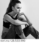 Купить «Young woman wearing black bra and blue jeans sitting on floor. Studio shot.», фото № 28533990, снято 25 июля 2017 г. (c) Ingram Publishing / Фотобанк Лори