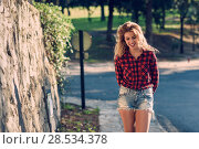 Купить «Beautiful woman with long blond curly hair. Enjoyment. Expressive Woman in checkered shirt and blue jeans with toothy Smile», фото № 28534378, снято 14 ноября 2015 г. (c) Ingram Publishing / Фотобанк Лори