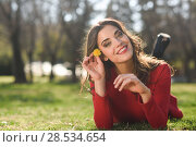 Купить «Portrait of young woman rest in the park with a dandelion in her hair, lying on the grass», фото № 28534654, снято 10 марта 2015 г. (c) Ingram Publishing / Фотобанк Лори