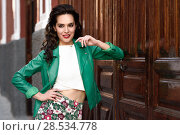 Купить «Young brunette woman, model of fashion, wearing green modern jacket and flower pants. Pretty caucasian girl with long wavy hairstyle smiling. Female with red lips in urban background.», фото № 28534778, снято 11 марта 2017 г. (c) Ingram Publishing / Фотобанк Лори