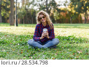 Young happy Woman in checkered shirt and blue jeans with toothy Smile and sunglasses. Blonde girl drinking coffee in park sitting on grass wearing casual clothes smiling. Стоковое фото, фотограф Javier Sánchez Mingorance / Ingram Publishing / Фотобанк Лори