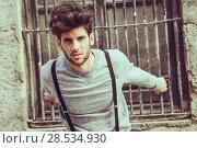 Купить «Portrait of young man wearing suspenders in urban background», фото № 28534930, снято 8 апреля 2014 г. (c) Ingram Publishing / Фотобанк Лори