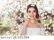 Portrait of young woman smiling in the flowered garden in the spring time. Almond flowers blossoms. Girl dressed in white like a bride. Стоковое фото, фотограф Javier Sánchez Mingorance / Ingram Publishing / Фотобанк Лори