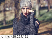 Close-up portrait of young blonde woman standing in a park with autumn colors. Beautiful girl wearing winter gray dress and wool cap. Female with straight hair and blue eyes. Стоковое фото, фотограф Javier Sánchez Mingorance / Ingram Publishing / Фотобанк Лори