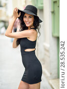 Купить «Brunette woman, model of fashion, wearing black seductive dress and sun hat in the street. Young girl with curly hairstyle walking in urban background», фото № 28535242, снято 7 июля 2016 г. (c) Ingram Publishing / Фотобанк Лори