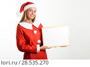 Купить «Beautiful happy blonde woman in Santa Claus clothes smiling with white board in her hands. Young female with blue eyes, isolated on white», фото № 28535270, снято 23 августа 2017 г. (c) Ingram Publishing / Фотобанк Лори